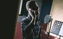 Homme dans le studio d'enregistrement parlant par le téléphone photos stock