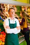 Homme dans le supermarché comme employé de magasin Photos libres de droits