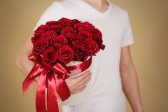 Homme dans le T-shirt blanc tenant le bouquet riche disponible de cadeau du rouge 21 Photo libre de droits