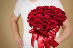Homme dans le T-shirt blanc tenant le bouquet riche disponible de cadeau du rouge 21 Photographie stock