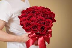 Homme dans le T-shirt blanc tenant le bouquet riche disponible de cadeau du rouge 21 Photos stock