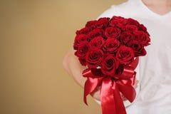 Homme dans le T-shirt blanc tenant le bouquet riche disponible de cadeau du rouge 21 Photo stock