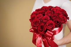 Homme dans le T-shirt blanc tenant le bouquet riche disponible de cadeau du rouge 21 Images stock