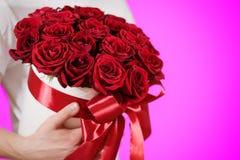 Homme dans le T-shirt blanc tenant le bouquet riche disponible de cadeau du rouge 21 Photographie stock libre de droits