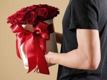 Homme dans le T-shirt noir tenant le bouquet riche disponible de cadeau du rouge 21 Photos stock