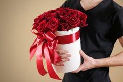 Homme dans le T-shirt noir tenant le bouquet riche disponible de cadeau du rouge 21 Image stock