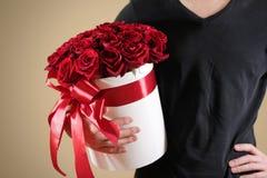 Homme dans le T-shirt noir tenant le bouquet riche disponible de cadeau du rouge 21 Photographie stock