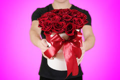 Homme dans le T-shirt noir tenant le bouquet riche disponible de cadeau du rouge 21 Image libre de droits