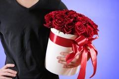 Homme dans le T-shirt noir tenant le bouquet riche disponible de cadeau du rouge 21 Photo stock