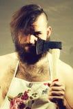 Homme dans le tablier de femme au foyer avec la hache photo stock