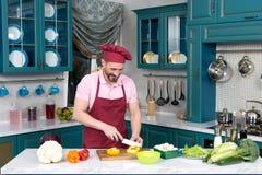 Homme dans le tablier rouge et le chapeau rouge coupant le paprika frais par le couteau photographie stock libre de droits