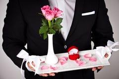 Homme dans le tenue de soirée avec la bague de fiançailles et les fleurs photo libre de droits