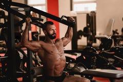 Homme dans le thème de sport Sportif établissant dans le gymnase Bodybuilder musculaire faisant des exercices images stock