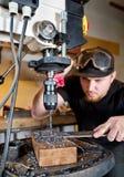 Homme dans le travail sur la foreuse à colonne électrique Photographie stock