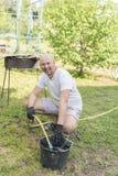homme dans le tuyau de seau de jardin Photo verticale Images stock