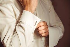 Homme dans les boutons de manchette blancs ordonnés de fixation de chemise soigneusement photos libres de droits