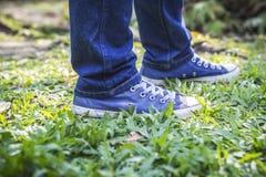 Homme dans les espadrilles bleues et des jeans se tenant sur l'herbe verte Images stock