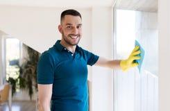 Homme dans les gants en caoutchouc nettoyant la fenêtre avec du chiffon Photographie stock libre de droits