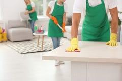 Homme dans les gants nettoyant la table à l'intérieur, photo stock