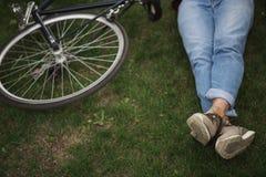 Homme dans les jeans et des espadrilles se trouvant avec la bicyclette sur la pelouse verte Photos libres de droits
