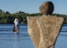Homme dans les pierres de équilibrage de fleuve Photos stock