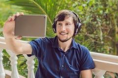 Homme dans les tropiques parlant avec les amis et la famille à l'appel visuel utilisant un comprimé et des écouteurs sans fil Image libre de droits