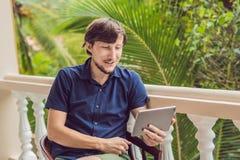 Homme dans les tropiques parlant avec les amis et la famille à l'appel visuel utilisant un comprimé et des écouteurs sans fil Photographie stock libre de droits