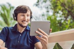 Homme dans les tropiques parlant avec les amis et la famille à l'appel visuel utilisant un comprimé et des écouteurs sans fil Photo stock