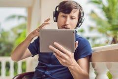 Homme dans les tropiques parlant avec les amis et la famille à l'appel visuel utilisant un comprimé et des écouteurs sans fil Photos stock