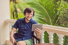 Homme dans les tropiques parlant avec les amis et la famille à l'appel visuel utilisant un comprimé et des écouteurs sans fil Photo libre de droits