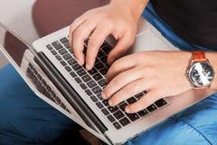 Homme dans les vêtements décontractés dactylographiant sur l'ordinateur portable Photo stock