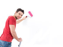 Homme dans occasionnel avec le rouleau et le mur de peinture Photographie stock libre de droits