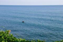 Homme dans un bateau à la mer bleue photographie stock