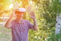 Homme dans un casque de réalité virtuelle dans la perspective de nature Mains vers le haut Photos stock