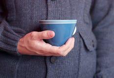 Homme dans un chandail de laine avec la tasse de café Images stock