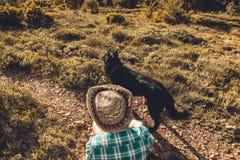 Homme dans un chapeau avec son chien dans le domaine Photographie stock