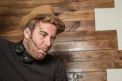 Homme dans un chapeau et des écouteurs faisant les visages drôles image libre de droits