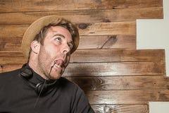 Homme dans un chapeau et des écouteurs faisant les visages drôles images stock