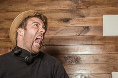 Homme dans un chapeau et des écouteurs faisant les visages drôles photographie stock libre de droits