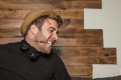 Homme dans un chapeau et des écouteurs faisant les visages drôles photos libres de droits
