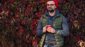 Homme dans un chapeau rouge avec une tasse dans des ses mains buvant du thé ou du café dehors Croissant doux et une cuvette de ca clips vidéos