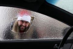Homme dans un chapeau rouge de Santa Claus dans une voiture avec le verre cassé Images stock