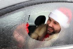 Homme dans un chapeau rouge de Santa Claus dans une voiture avec le verre cassé Image stock