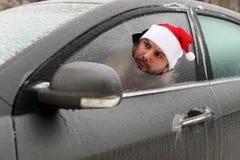 Homme dans un chapeau rouge de Santa Claus dans une voiture avec le verre cassé Photo stock