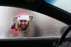 Homme dans un chapeau rouge de Santa Claus dans une voiture avec le verre cassé Images libres de droits