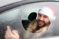 Homme dans un chapeau rouge de Santa Claus dans une voiture avec le verre cassé Photos libres de droits