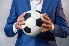 Homme dans un costume avec du ballon de football photographie stock