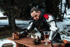 Homme dans un costume historique avec un verre en bois à la table images stock