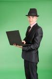 Homme dans un costume noir avec un ordinateur portable Photos libres de droits