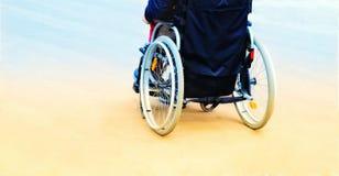 Homme dans un fauteuil roulant tout en marchant la rue modifiant la tonalité, vue arrière photos stock